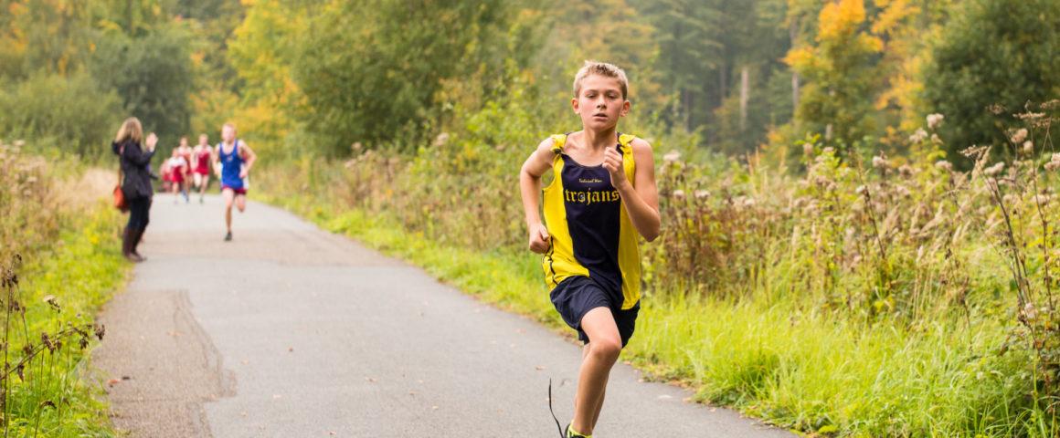 garoto com roupa de esporte correndo em pista asfaltada física