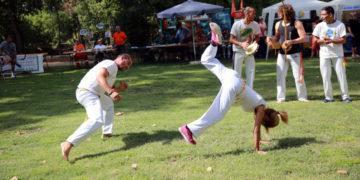menino menina jogando capoeira berimbau