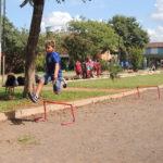 menino pula obstáculos em pista de terra
