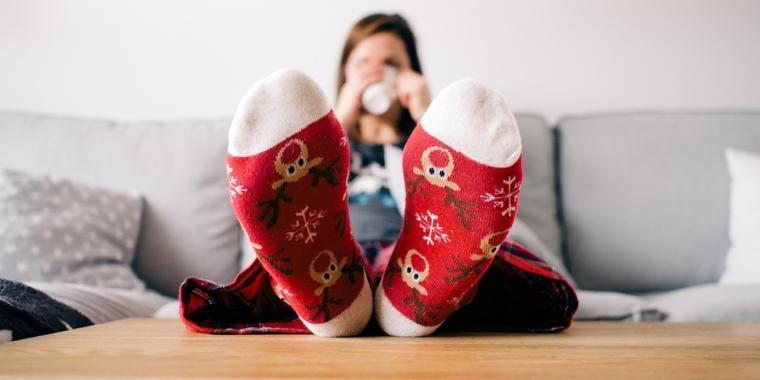 Moça sentada no sofá com uma caneca, vestindo pijama com os pés e meias em cima da mesa
