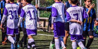 Jovens jogadores de futebol apertam as mãos do adversário na entrada do gramado