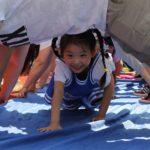 Pequena criança asiática engatinha sorrindo por baixo de adultos apoiados em forma de arco