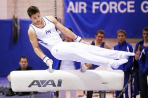 atleta homem vestido de branco seguro nas duas alças sobre uma barra horizontal e ergue seu corpo na direção esquerda com as pernas esticadas sem tocar na barra