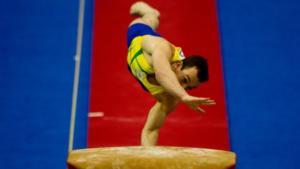 atleta com camisa amarela e short azul apoia mão esquerda sobre trampolim para saltar