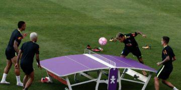 Neymar bate na bola com a cabeça em uma mesa semelhante a de ping pong com dois atletas da seleção brasileira do lado oposto e um ao seu lado