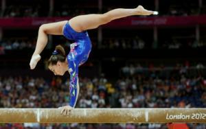 Atleta faz contorcionismo na trave olímpica, com as mãos apoiadas na trave e as pernas em direções opostas no ar formando um ângulo de quase 180 graus com elas
