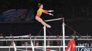 Jovem atleta parece voar de uma barra para a outra