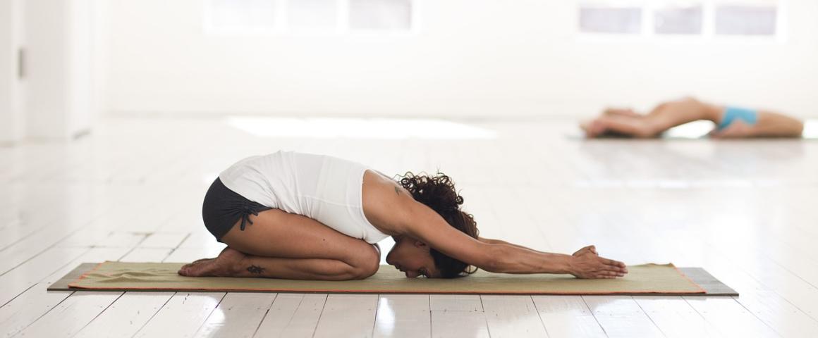 mulher em sala bastante branca faz posição de yoga sentada no chão com as mãos esticadas para frente e a cabeça para baixo