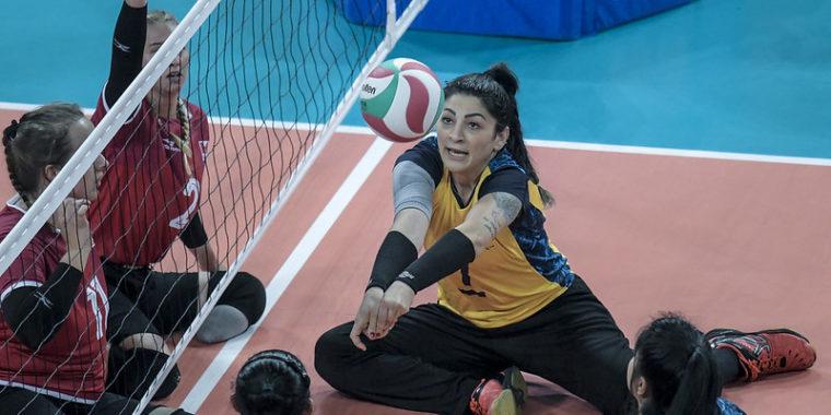 atleta feminina da seleção brasileira de vôlei sentado na vitória contra o Canadá no Parapan