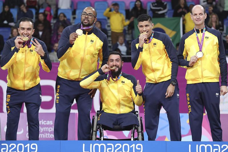 atletas brasileiros de vôlei sentado celebram mordendo medalha de ouro