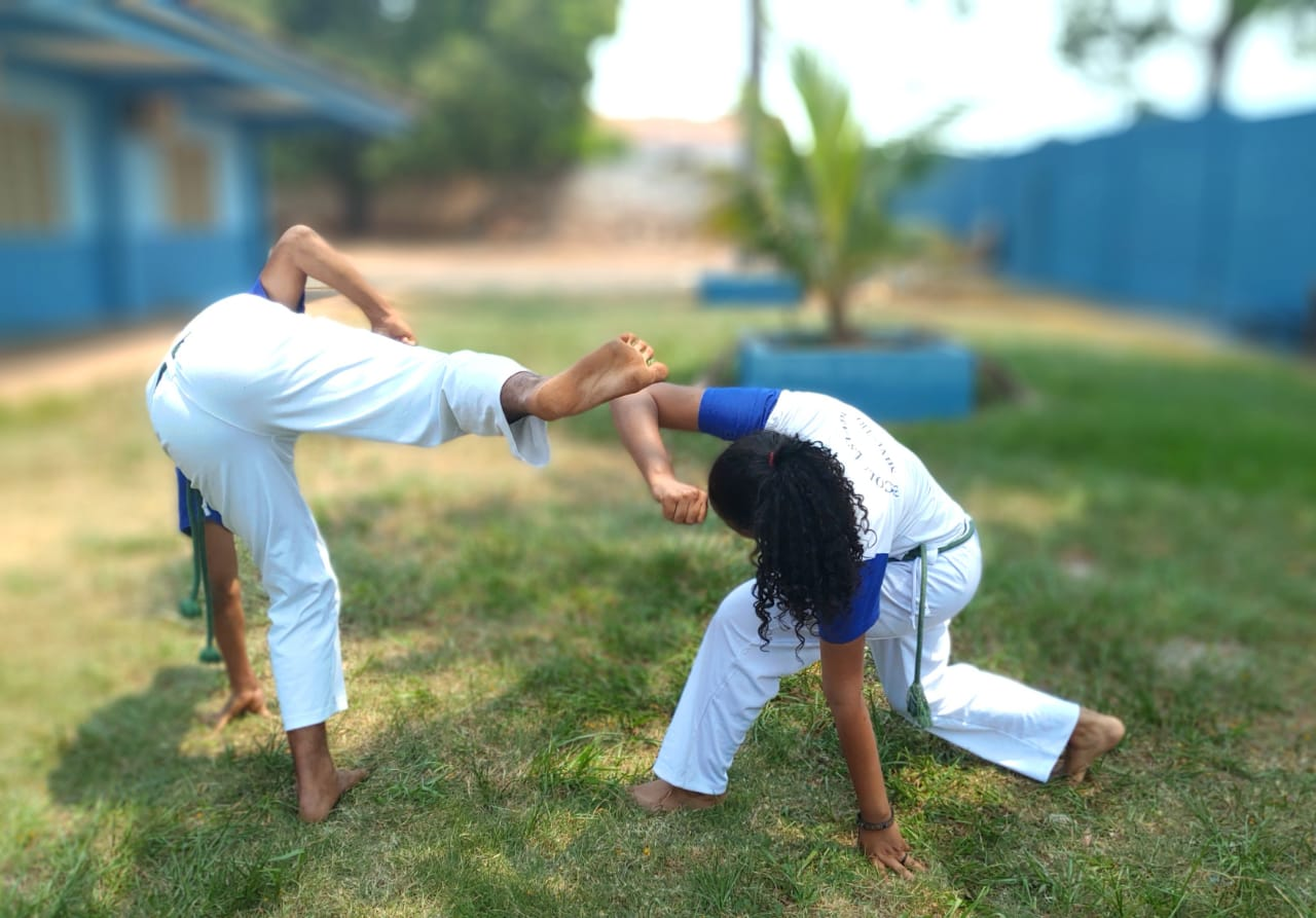 dois jovens jogam capoeira, ele com a perna pro lado e ela abaixando