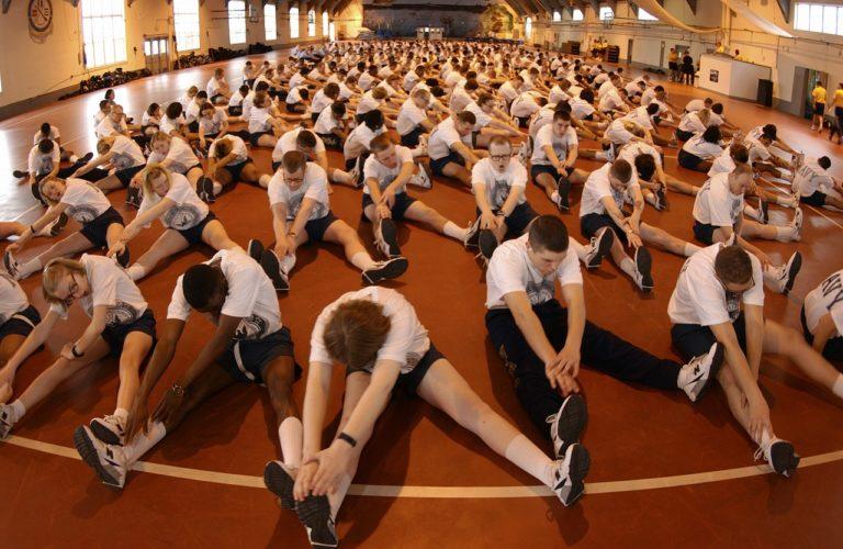 treinamento funcional: grupo com dezenas de homens sentados no chão se alongando