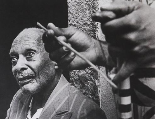 foto em preto e branco do mestre de capoeira pastinha com berimbau no primeiro plano