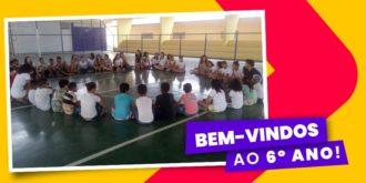alunos do 6º ano sentados em círculo no centro da quadra com lettering bem-vindos