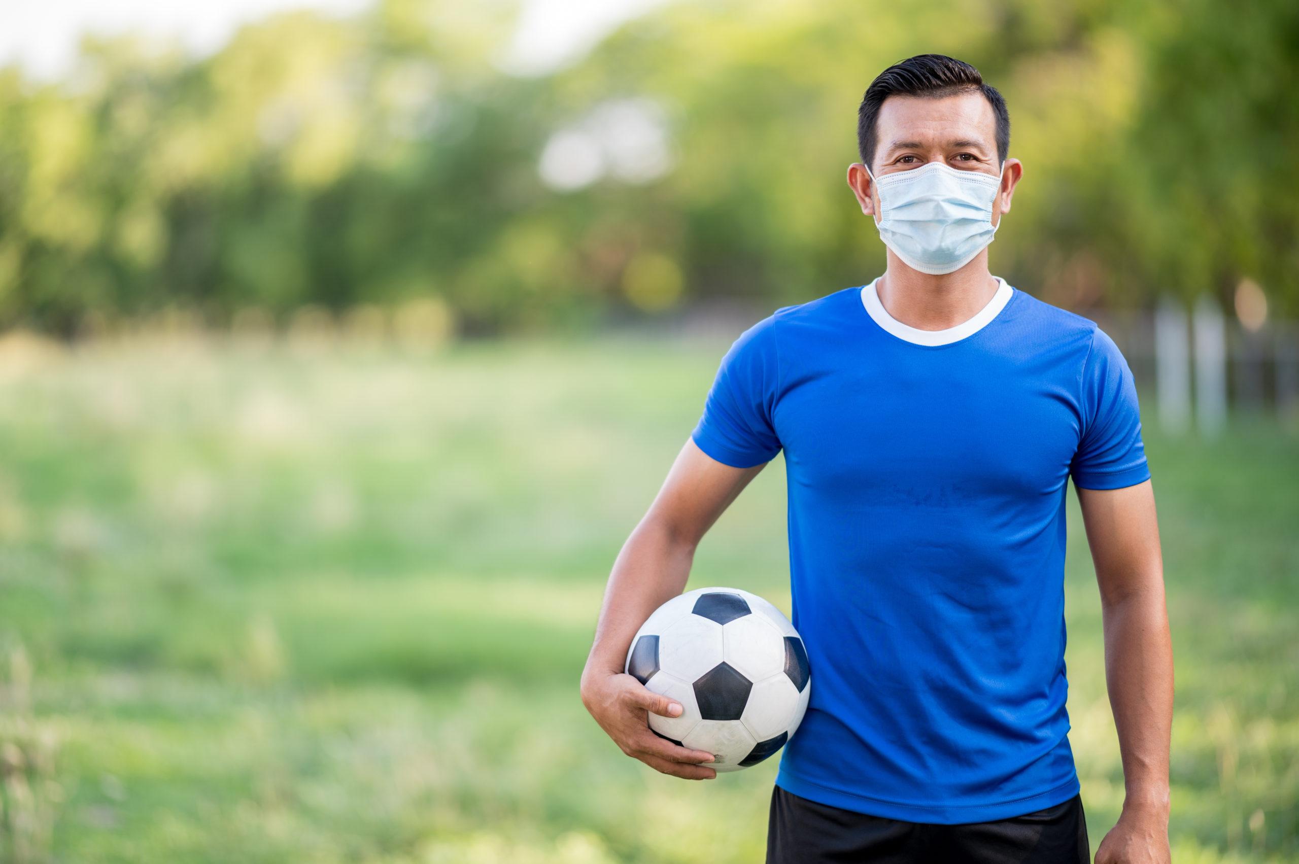 homem camisa azul e máscara segurando bola de futebol